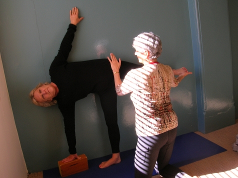 Assisting student in Ardha Chandrasana (Half Moon Pose)